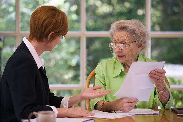 An image of an old woman talking to a lawyer about her will